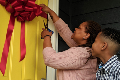 Angel cuts the ribbon to her new home