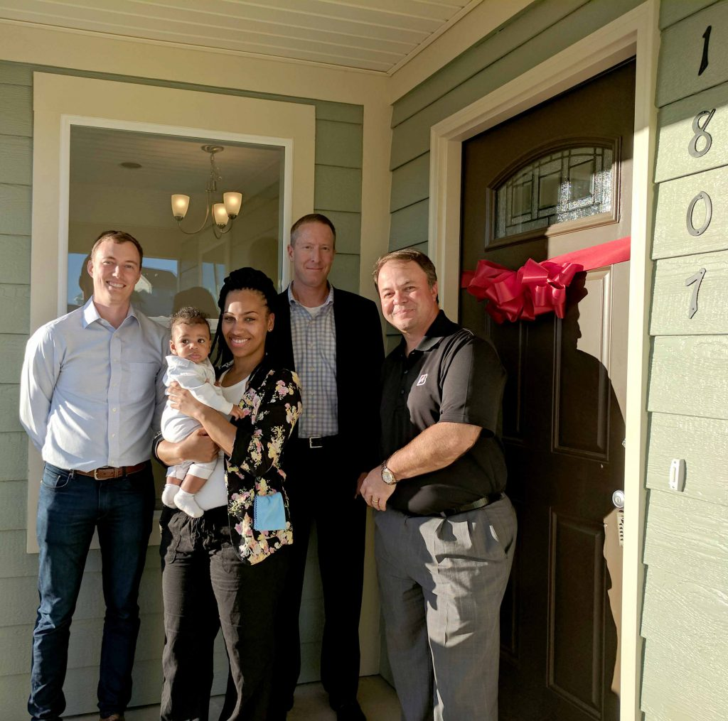 Dan Cox, Justin Reinke, and Brian Cunningham from Bridgestone, with Sharniece Rayford and her son, Kamdyn Grayson