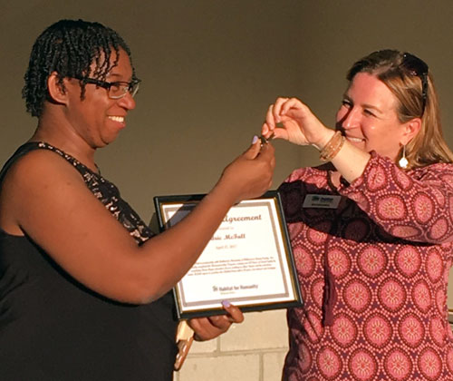 Director of Development Kim Randell hands Sedric McFall her mortgage certificate and keys.